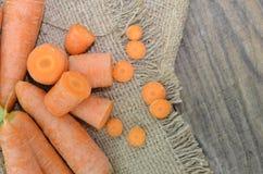 Φρέσκες καρότα και περικοπές στο ακατέργαστο ύφασμα στο ξύλινο υπόβαθρο, κινηματογράφηση σε πρώτο πλάνο Στοκ Εικόνα