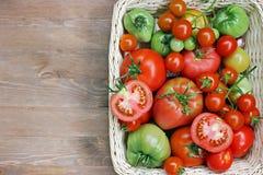 Φρέσκες κόκκινες και πράσινες ντομάτες σε ένα καλάθι σε έναν πίνακα Στοκ Φωτογραφία