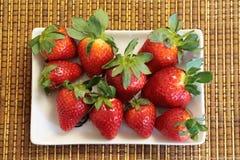 Κόκκινες φράουλες στο άσπρο πιάτο στοκ εικόνες
