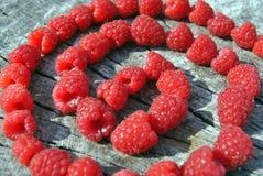 Φρέσκες κόκκινες φυσικές μορφές στροβίλου σμέουρων, στο παλαιό ραγισμένο ξύλινο υπόβαθρο Στοκ Εικόνες