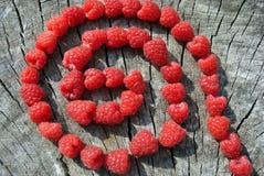 Φρέσκες κόκκινες φυσικές μορφές στροβίλου σμέουρων στο παλαιό ραγισμένο ξύλινο υπόβαθρο Στοκ φωτογραφία με δικαίωμα ελεύθερης χρήσης
