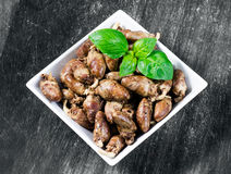 Φρέσκες μαγειρευμένες καρδιές κοτόπουλου που καρυκεύονται με το πιπέρι και το αλάτι έτοιμα να φάνε διακόσμηση φύλλων βασιλικού Αν στοκ εικόνες