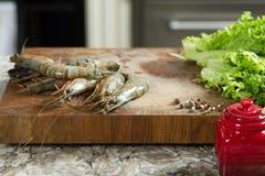 Φρέσκες μαύρες γαρίδες τιγρών έτοιμες για την προετοιμασία σε ένα αγροτικό ξύλινο πιπέρι πινάκων Στοκ Εικόνες