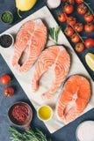 Φρέσκες μπριζόλες σολομών, χορτάρια, ελαιόλαδο και μαγειρεύοντας συστατικά στο μαρμάρινο υπόβαθρο στοκ εικόνες
