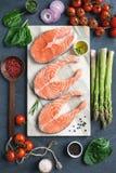 Φρέσκες μπριζόλες σολομών, χορτάρια, ελαιόλαδο και μαγειρεύοντας συστατικά στο μαρμάρινο υπόβαθρο στοκ εικόνα