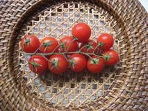 Φρέσκες ντομάτες κερασιών σε έναν μίσχο σε ένα ψάθινο πιάτο στοκ εικόνες