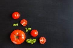 Φρέσκες ντομάτες κερασιών σε ένα μαύρο υπόβαθρο πινάκων κιμωλίας με το χορτάρι Στοκ εικόνα με δικαίωμα ελεύθερης χρήσης