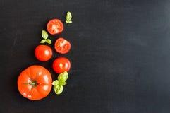 Φρέσκες ντομάτες κερασιών σε ένα μαύρο υπόβαθρο πινάκων κιμωλίας με το χορτάρι Στοκ φωτογραφία με δικαίωμα ελεύθερης χρήσης