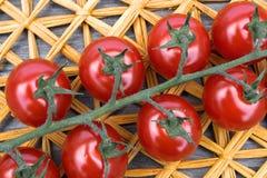 Φρέσκες ντομάτες κερασιών σε ένα υπόβαθρο ενός χαλιού αχύρου Στοκ Φωτογραφία