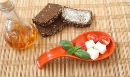 Φρέσκες ντομάτες κερασιών, ψωμί, chees, προέχον και πιπέρι τσίλι στο κόκκινο πιάτο Στοκ Φωτογραφία
