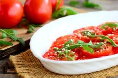 Φρέσκες ντομάτες, σαλάτα rucola και σουσαμιού Θερινή φυτική σαλάτα σε ένα άσπρο κλωστοϋφαντουργικό προϊόν πιάτων και burlap Στοκ Εικόνες
