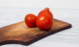 Φρέσκες ντομάτες στον εκλεκτής ποιότητας ξύλινο τέμνοντα πίνακα και το ξύλινο υπόβαθρο Στοκ εικόνα με δικαίωμα ελεύθερης χρήσης
