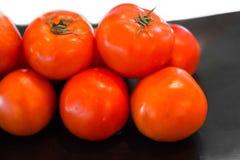 Φρέσκες ντομάτες στο μαύρο πιάτο Στοκ Εικόνες