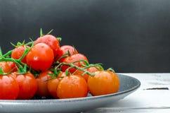 Φρέσκες ντομάτες στο μαύρο πιάτο Στοκ Εικόνα