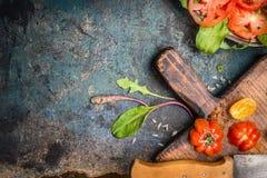 Φρέσκες ντομάτες, τέμνοντες πίνακας και μαχαίρι κουζινών στο σκοτεινό αγροτικό υπόβαθρο, τοπ άποψη Στοκ Φωτογραφίες