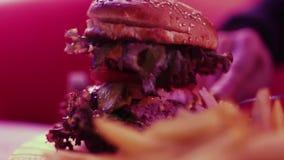 Φρέσκες νόστιμες burger και τηγανιτές πατάτες στον ξύλινο πίνακα HD φιλμ μικρού μήκους