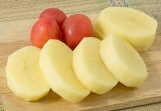 Φρέσκες πατάτες και ντομάτες στον ξύλινο πίνακα Στοκ φωτογραφίες με δικαίωμα ελεύθερης χρήσης