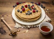 Φρέσκες τηγανίτες Hill σε ένα άσπρο πιάτο με την πετσέτα με το μέλι και το κουτάλι μελιού, τα διαφορετικά μούρα και ένα φλυτζάνι  Στοκ Εικόνες