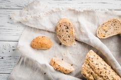 Φρέσκες, υγιείς ολόκληρες baguette και φέτες σίκαλης σιταριού στο ύφασμα Στοκ Εικόνες