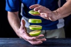 Φρέσκες φέτες μετεωρισμού ενός πράσινου μήλου, πέρα από έναν ξύλινο πίνακα Στοκ εικόνα με δικαίωμα ελεύθερης χρήσης