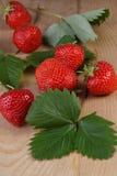 Φρέσκες φράουλες με τα φύλλα στην ξύλινη ανασκόπηση Στοκ Φωτογραφίες