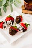 Φρέσκες φράουλες που βυθίζονται στις σκοτεινές νιφάδες W σοκολάτας και καρύδων Στοκ Εικόνες
