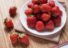 Φρέσκες φράουλες σε ένα κύπελλο στον ξύλινο πίνακα στοκ εικόνα