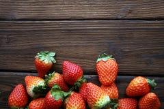 Φρέσκες φράουλες στο καφετί ξύλινο υπόβαθρο Μια ομάδα strawb Στοκ εικόνες με δικαίωμα ελεύθερης χρήσης