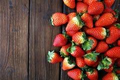 Φρέσκες φράουλες στο καφετί ξύλινο υπόβαθρο Μια ομάδα strawb Στοκ Εικόνες