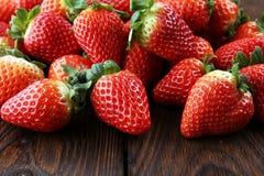 Φρέσκες φράουλες στο καφετί ξύλινο υπόβαθρο Μια ομάδα strawb Στοκ Εικόνα