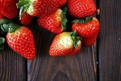 Φρέσκες φράουλες στο καφετί ξύλινο υπόβαθρο Μια ομάδα strawb Στοκ εικόνα με δικαίωμα ελεύθερης χρήσης