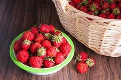 Φρέσκες φράουλες με ένα καλάθι στο ξύλινο υπόβαθρο Στοκ Φωτογραφία