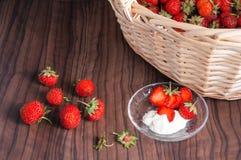 Φρέσκες φράουλες με ένα καλάθι στο ξύλινο υπόβαθρο Στοκ Εικόνα