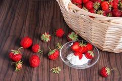 Φρέσκες φράουλες με ένα καλάθι στο ξύλινο υπόβαθρο Στοκ εικόνες με δικαίωμα ελεύθερης χρήσης