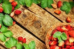 Φρέσκες φράουλες σε ένα καλάθι στον ξύλινο πίνακα με τα πράσινα laves στοκ εικόνες