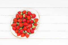 Φρέσκες φράουλες στο πιάτο στον άσπρο ξύλινο πίνακα Τοπ όψη Στοκ φωτογραφία με δικαίωμα ελεύθερης χρήσης