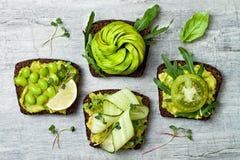 Φρέσκες φρυγανιές αβοκάντο με τα διαφορετικά καλύμματα Υγιές χορτοφάγο πρόγευμα με τα wholegrain σάντουιτς σίκαλης Στοκ Εικόνα