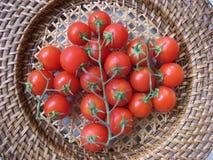 Φρέσκες ώριμες ντομάτες κερασιών σε ένα ψάθινο πιάτο Στοκ Εικόνες