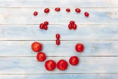 Φρέσκες ώριμες οργανικές κόκκινες οργανικές ντομάτες σε έναν μπλε ξύλινο πίνακα Στοκ Εικόνες