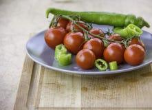Φρέσκες juicy κόκκινες φέτες ντοματών κερασιών του πράσινου καυτού πιπεριού στοκ εικόνα