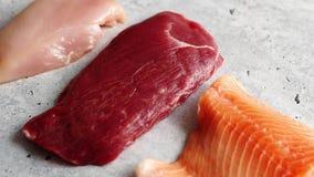 Φρέσκια ακατέργαστη μπριζόλα βόειου κρέατος, στήθος κοτόπουλου, και λωρίδα σολομών απόθεμα βίντεο