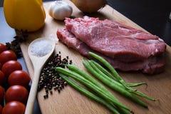 Φρέσκια ακατέργαστη μπριζόλα κρέατος με το καρύκευμα και λαχανικά στην ξύλινη επιφάνεια στοκ φωτογραφία