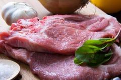 Φρέσκια ακατέργαστη μπριζόλα κρέατος με το καρύκευμα και λαχανικά στην ξύλινη επιφάνεια στοκ φωτογραφία με δικαίωμα ελεύθερης χρήσης