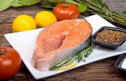 Φρέσκια ακατέργαστη μπριζόλα ψαριών σολομών κόκκινη με τα χορτάρια και τα λαχανικά Στοκ Εικόνες