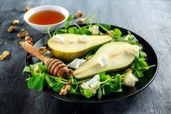 Φρέσκια γλυκιά σαλάτα αχλαδιών με τα ξύλα καρυδιάς, το μέλι και το άσπρο μαλακό τυρί στο μαύρο πιάτο Στοκ Εικόνες