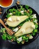 Φρέσκια γλυκιά σαλάτα αχλαδιών με τα ξύλα καρυδιάς, το μέλι και το άσπρο μαλακό τυρί στο μαύρο πιάτο Στοκ Φωτογραφία
