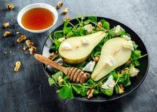 Φρέσκια γλυκιά σαλάτα αχλαδιών με τα ξύλα καρυδιάς, το μέλι και το άσπρο μαλακό τυρί στο μαύρο πιάτο Στοκ εικόνα με δικαίωμα ελεύθερης χρήσης