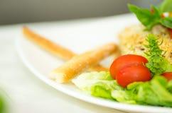 Φρέσκια ζωηρόχρωμη σαλάτα κινηματογραφήσεων σε πρώτο πλάνο με τις ντομάτες κερασιών, τα πράσινα veggies και μερικές κροτίδες που  Στοκ Εικόνες