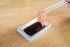 Φρέσκια ιαπωνική φέτα σολομών που τρώει με τη σάλτσα σόγιας στο ξύλινο υπόβαθρο Στοκ εικόνα με δικαίωμα ελεύθερης χρήσης