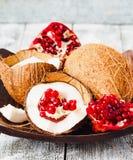 Φρέσκια καρύδα και κόκκινος γρανάτης σε ένα ξύλινο κύπελλο, μπλε υπόβαθρο Στοκ Φωτογραφίες